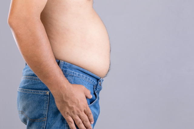 Close up fat man standing and show his tummy studio shot on grey background with copy space for text or design. Fat people and healthy concept